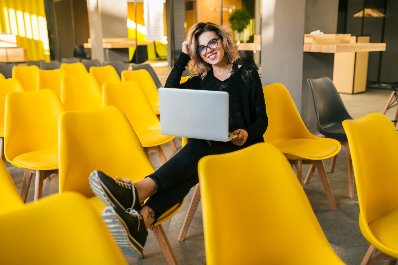 Woman with laptop on yellow chairs
