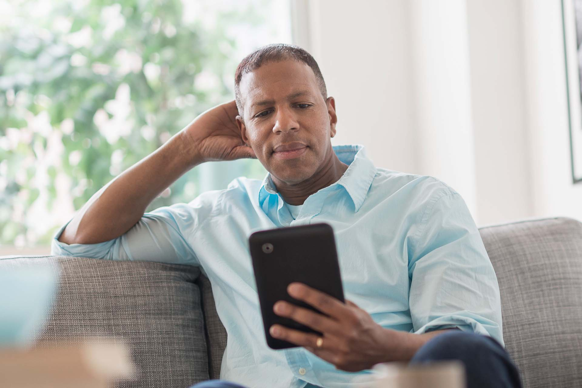 male on couch using tablet