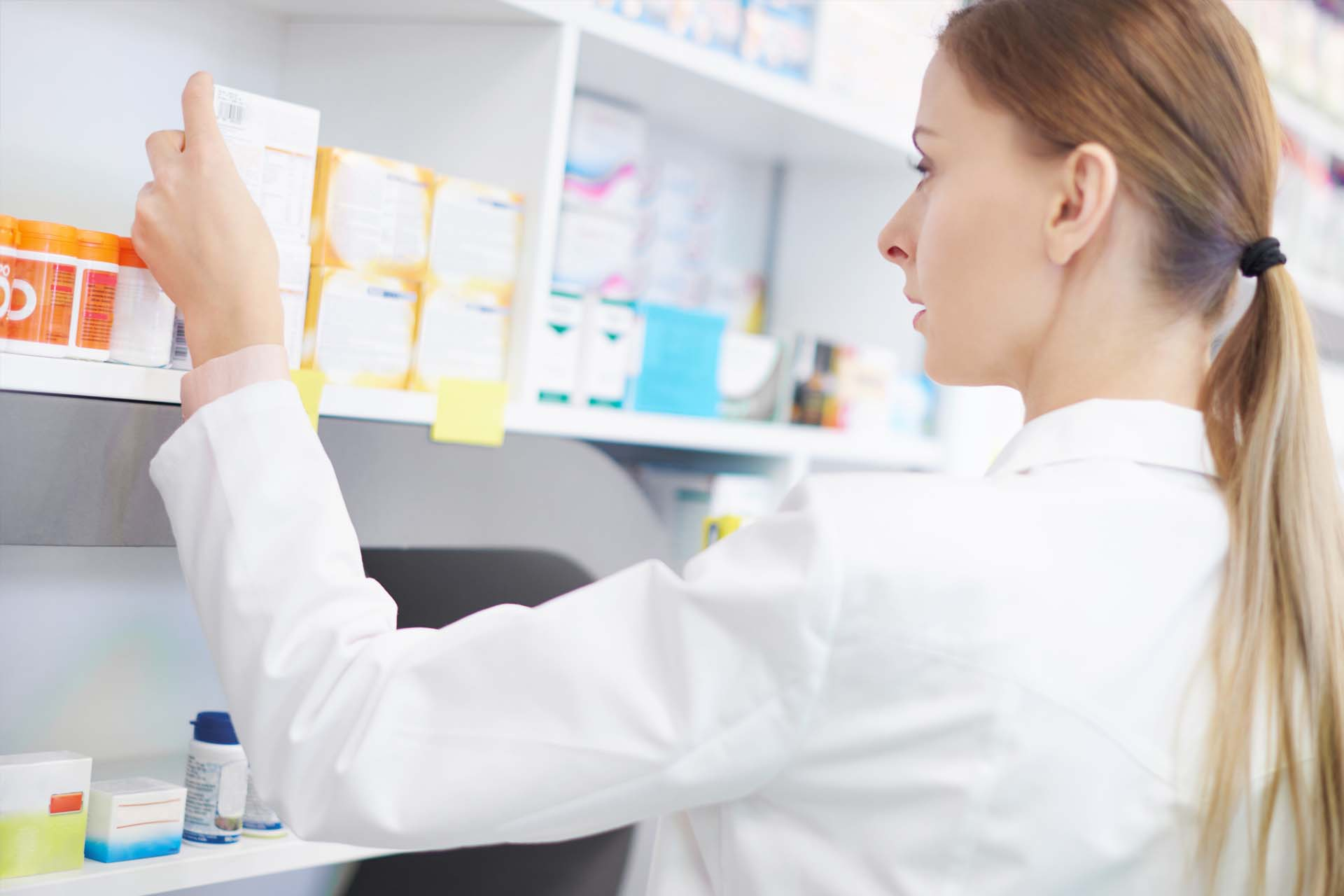 pharmacist examining medication in pharmacy