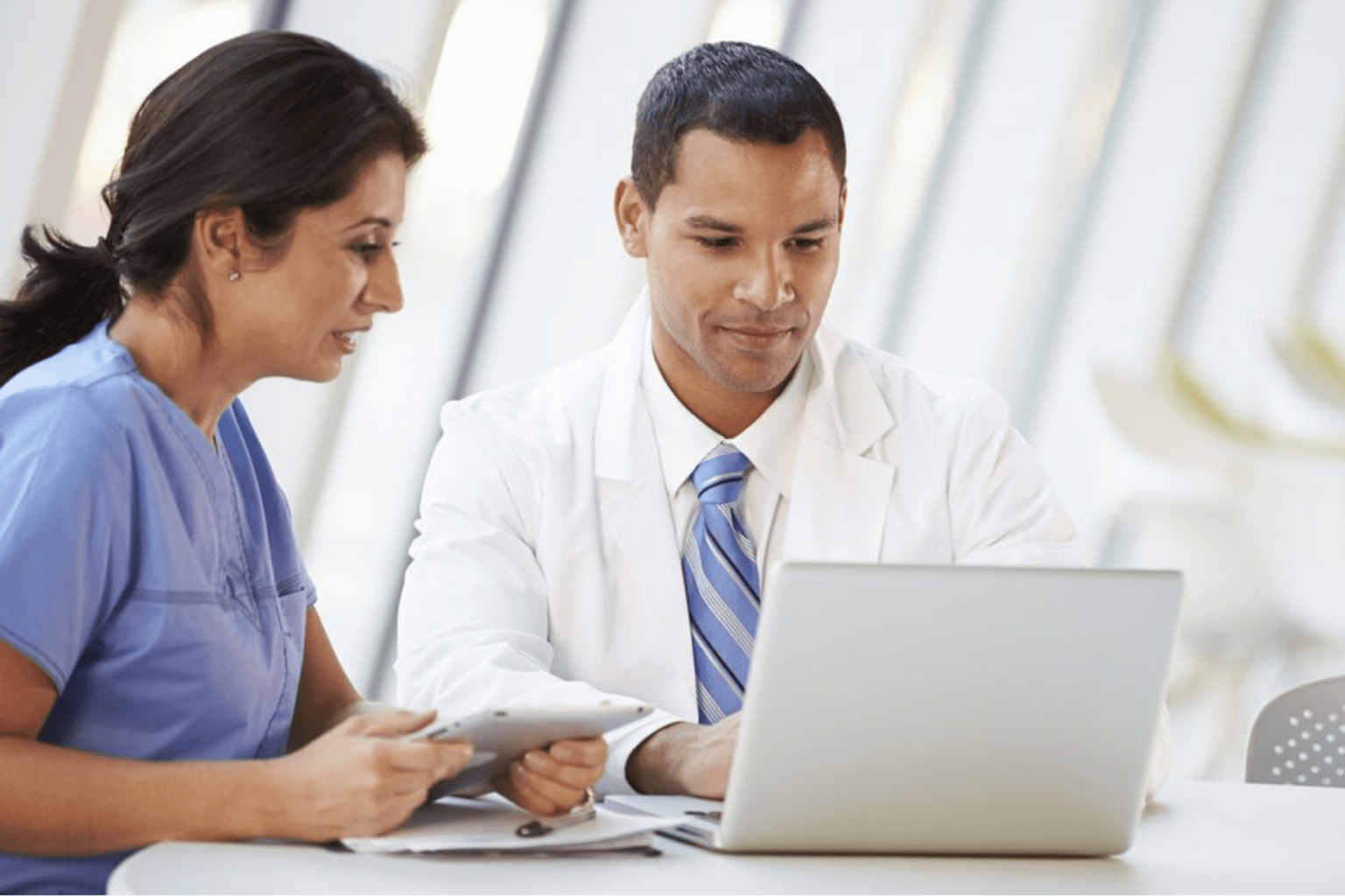 Two medical professionals looking at a laptop
