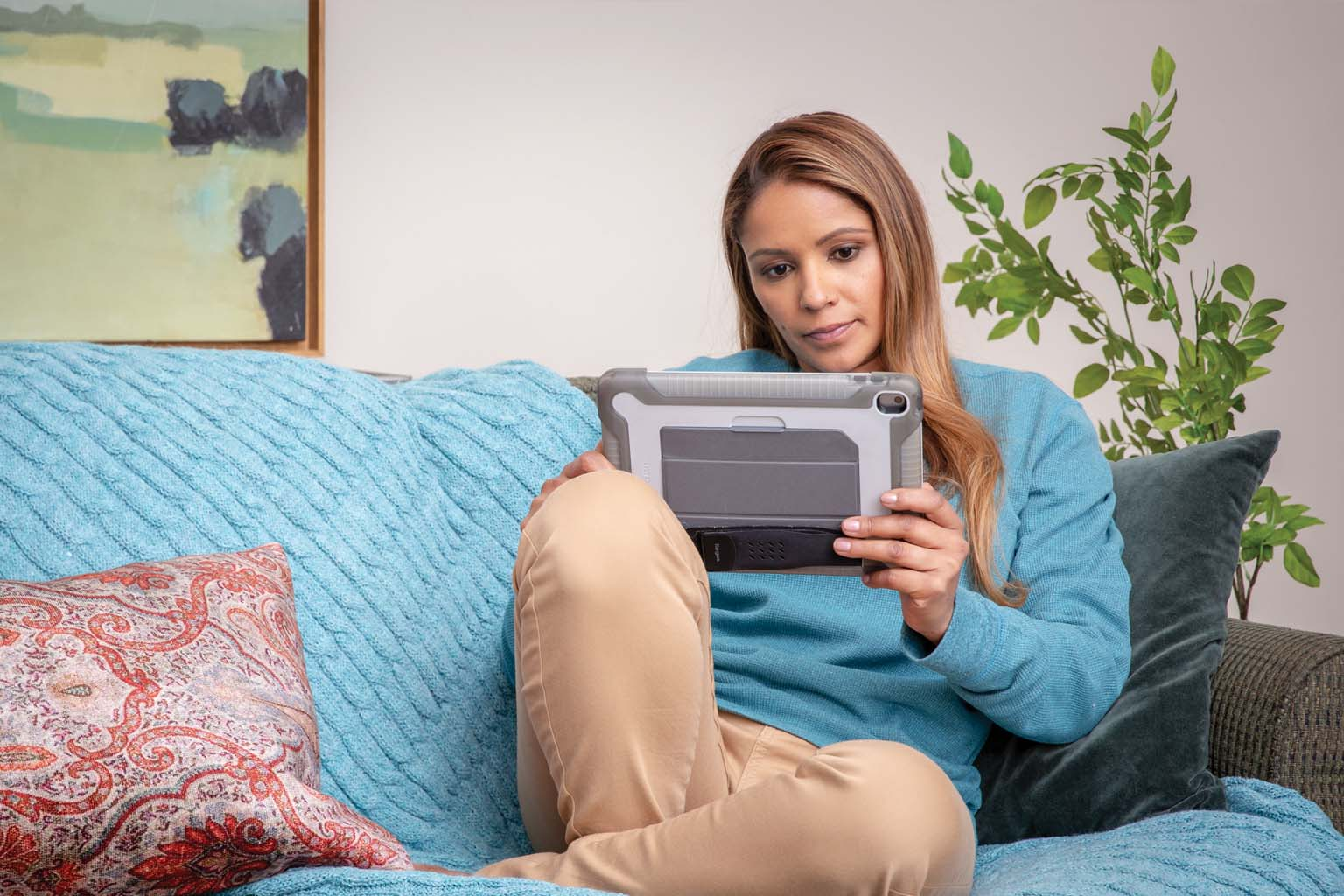 female crosslegged on couch with tablet