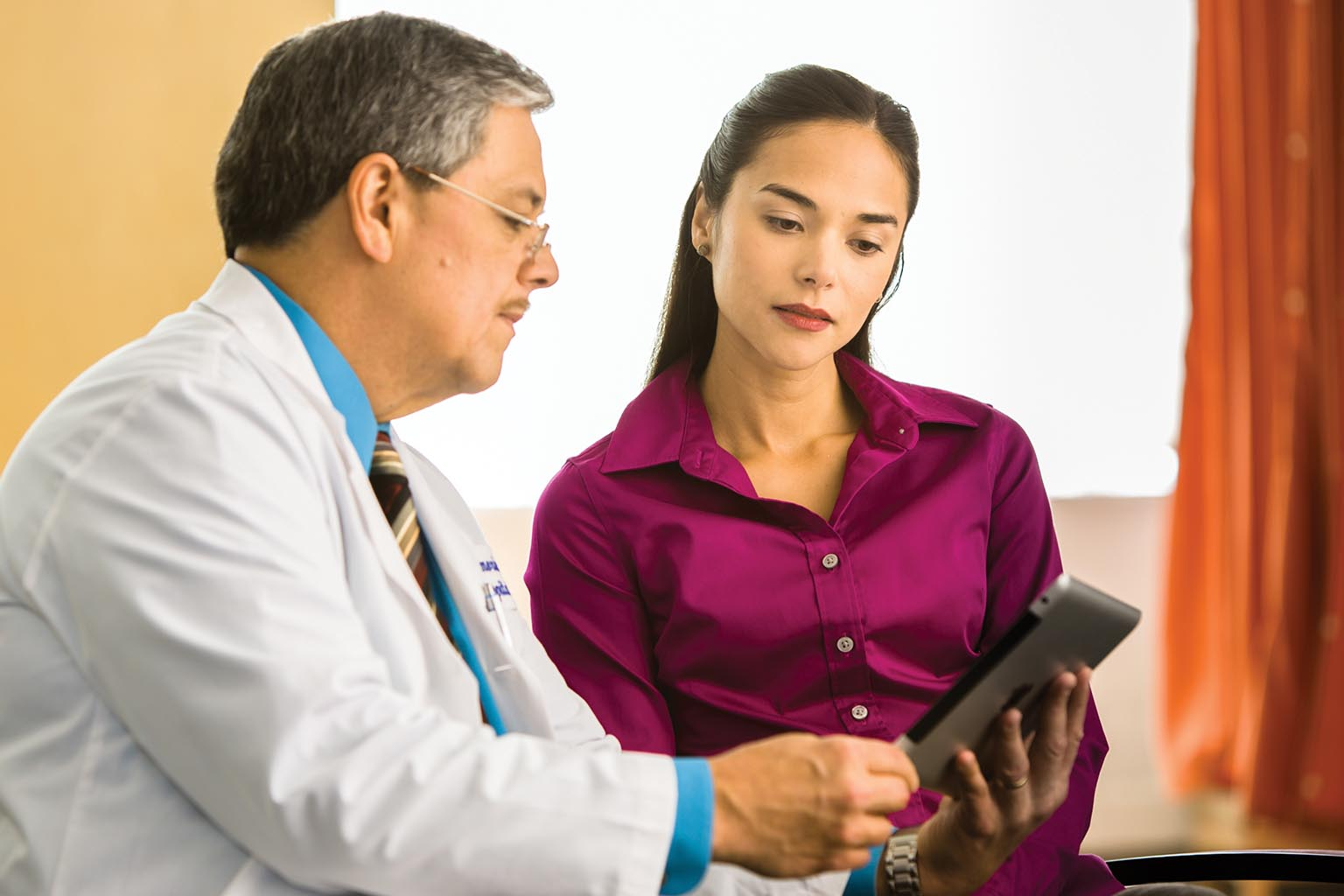 clinician with patient viewing tablet