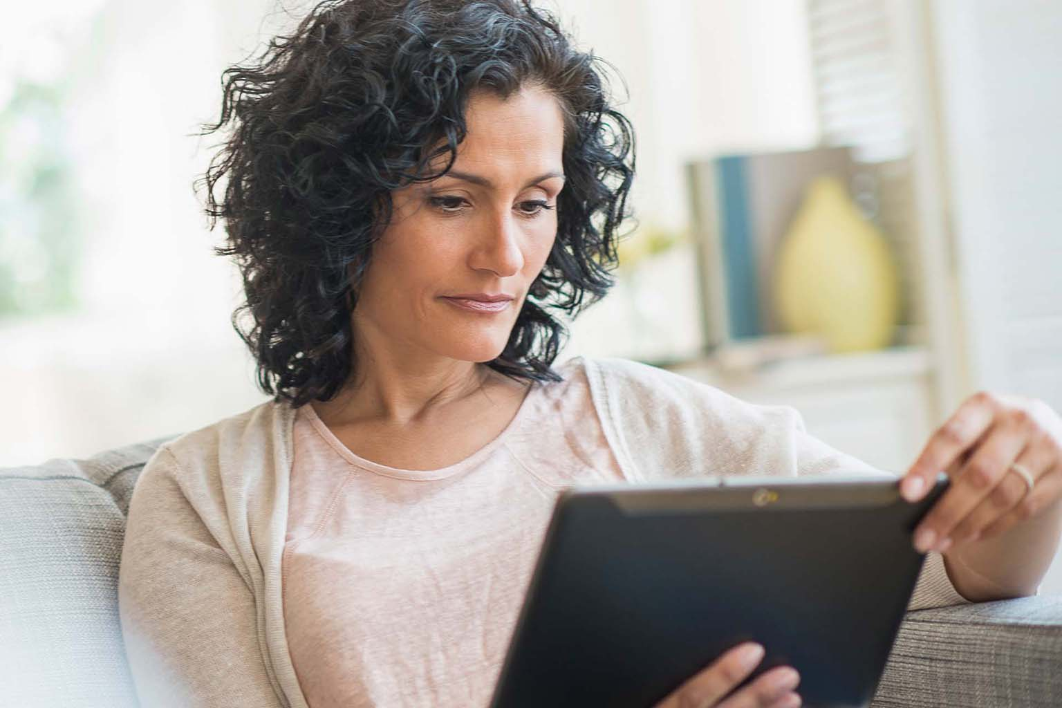 woman on couch using tablet