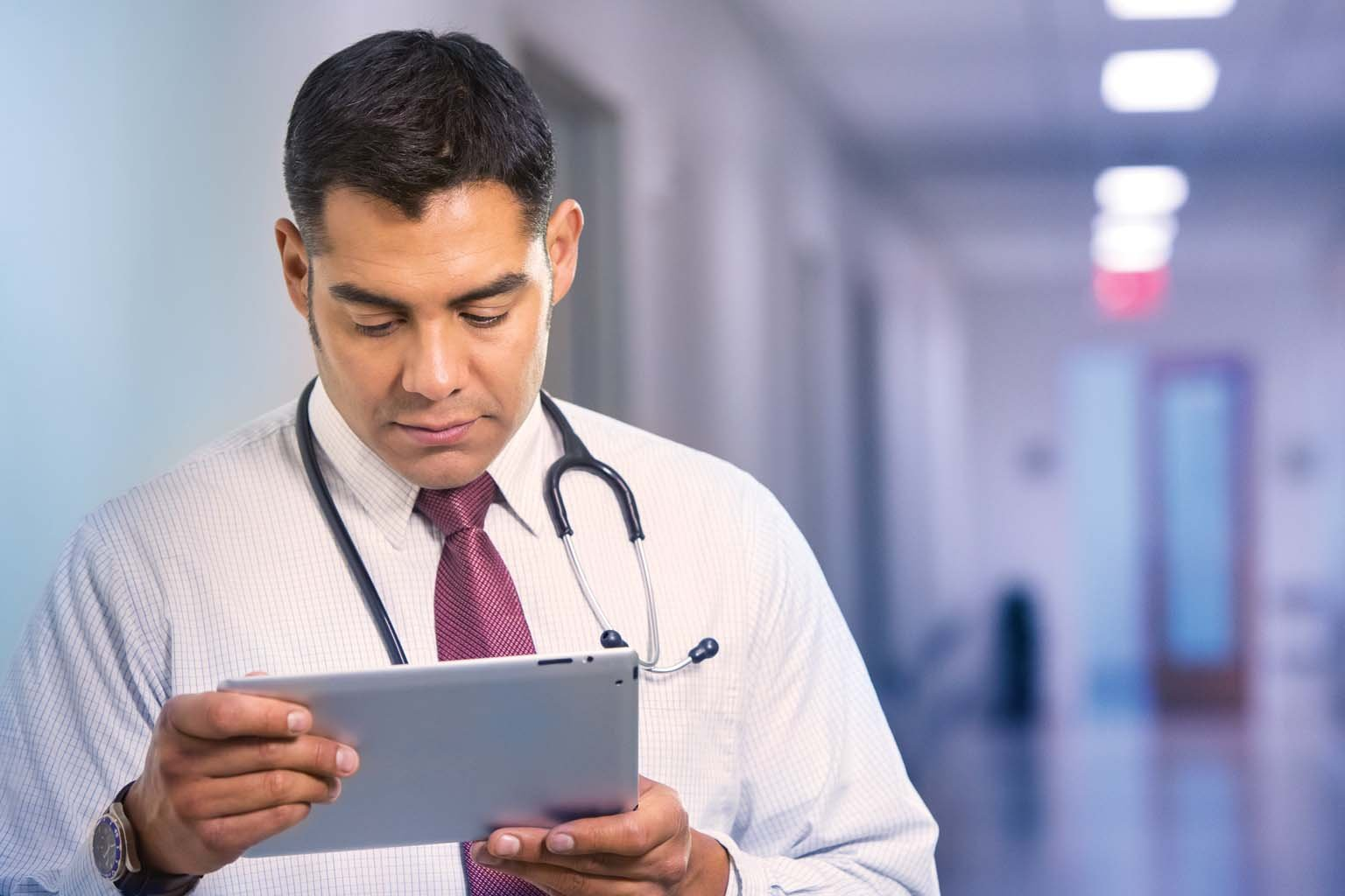 doctor paused in hallway looking at tablet