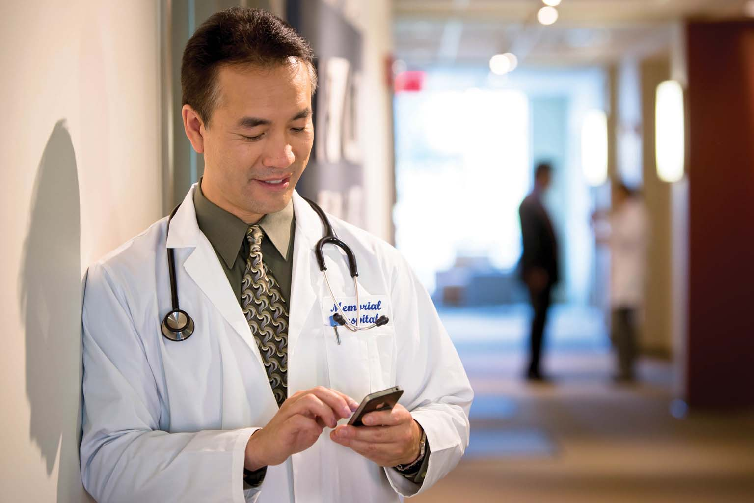 doctor paused in hallway looking at smartphone