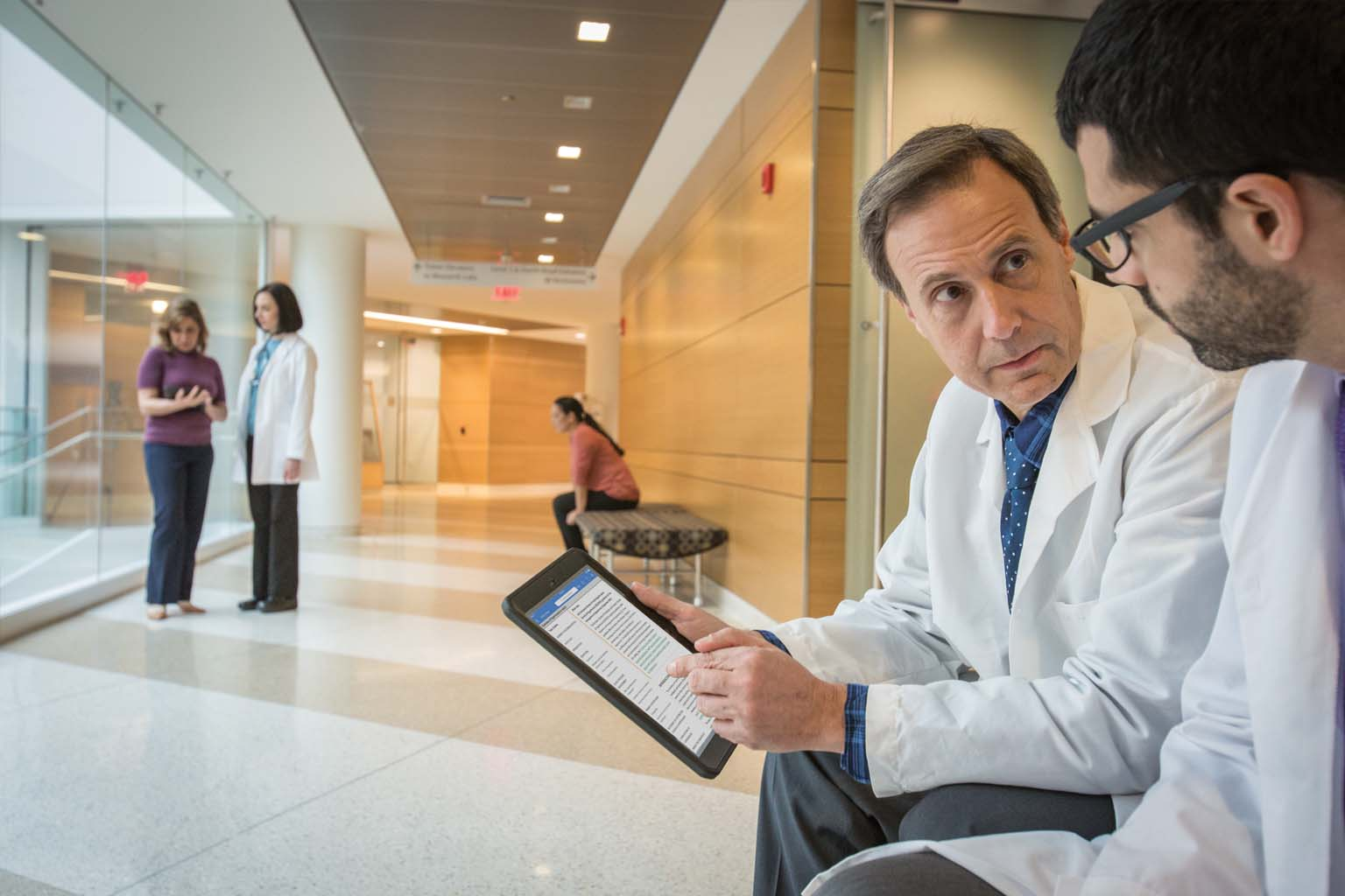 two doctors seated with tablet in hospital hallway