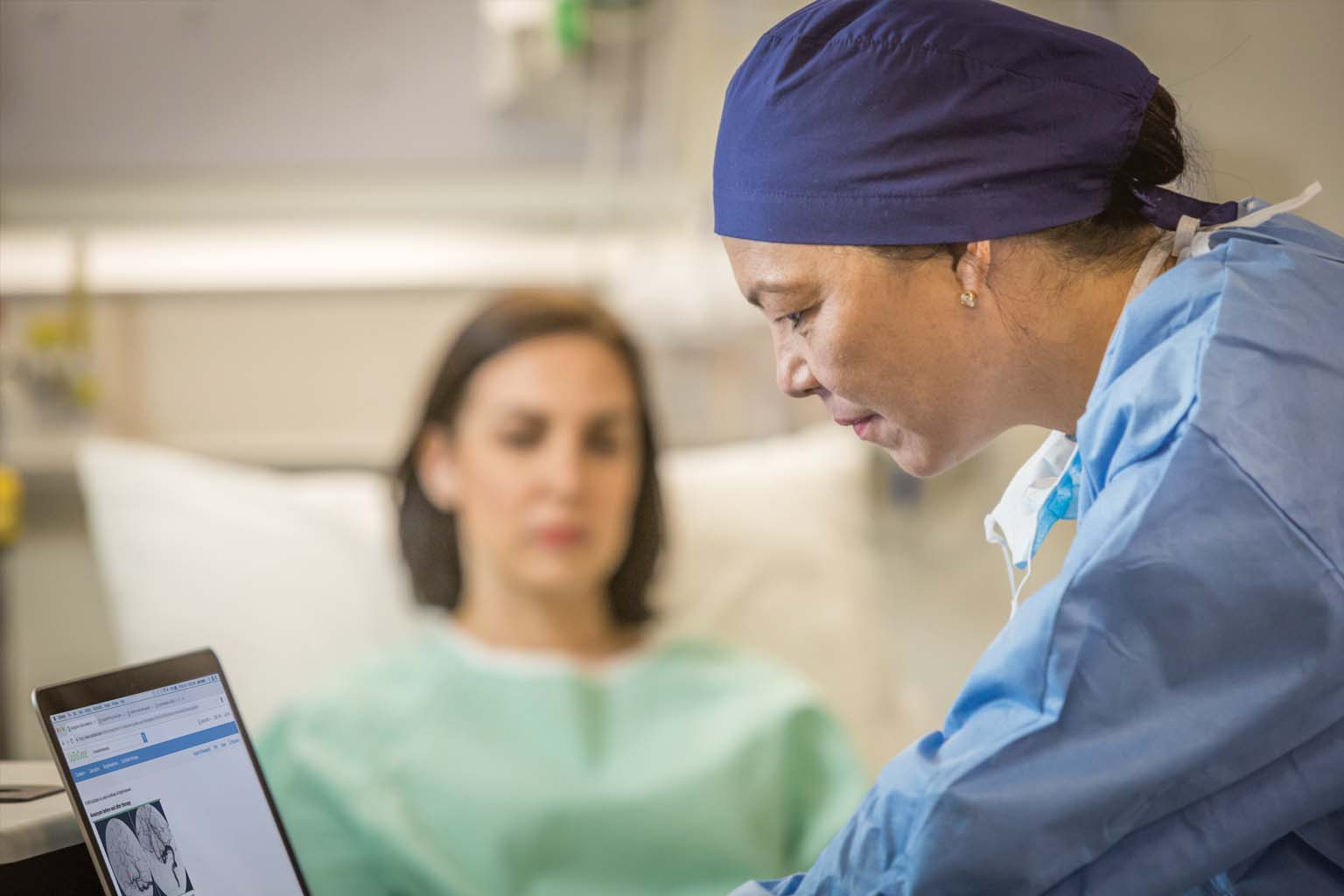 surgeon viewing UpToDate on laptop with patient in background