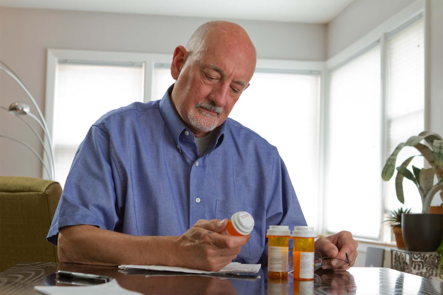man reading label on prescription bottle