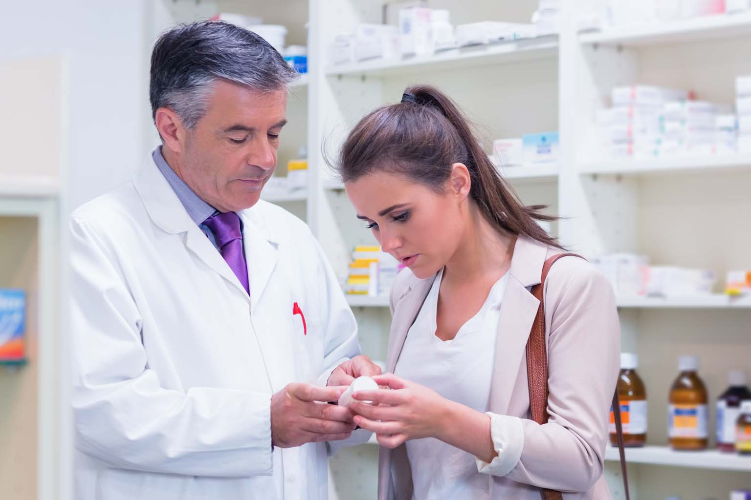 pharmacist in pharmacy talking to patient