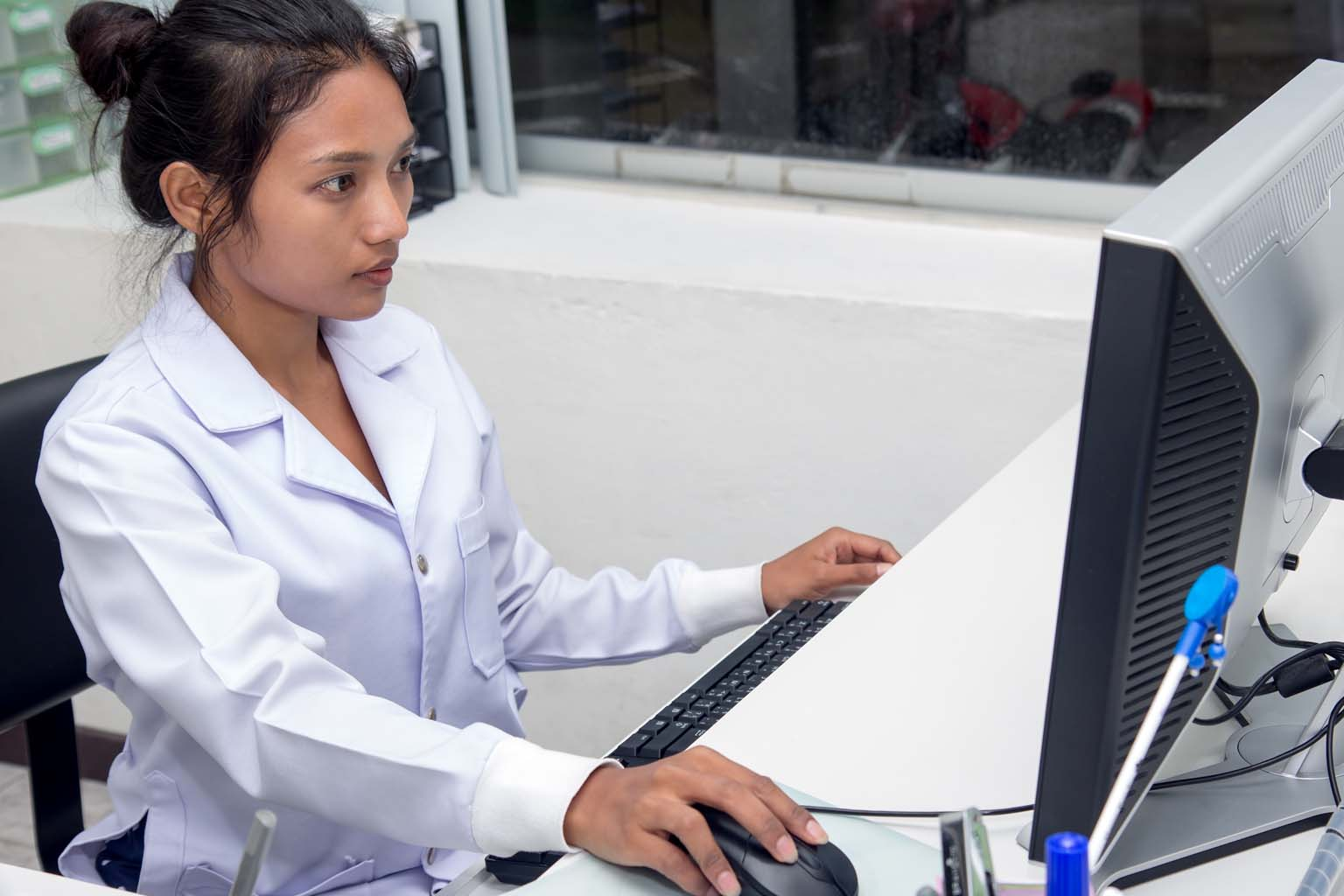 pharmacist using computer in pharmacy