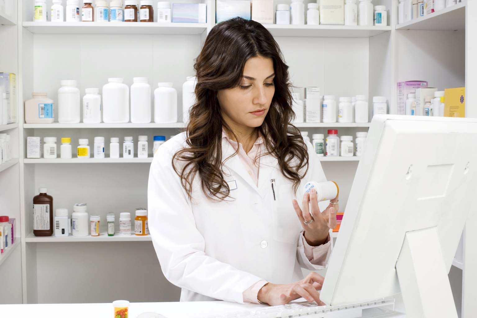 phamacist holding bottle of pills while using computer