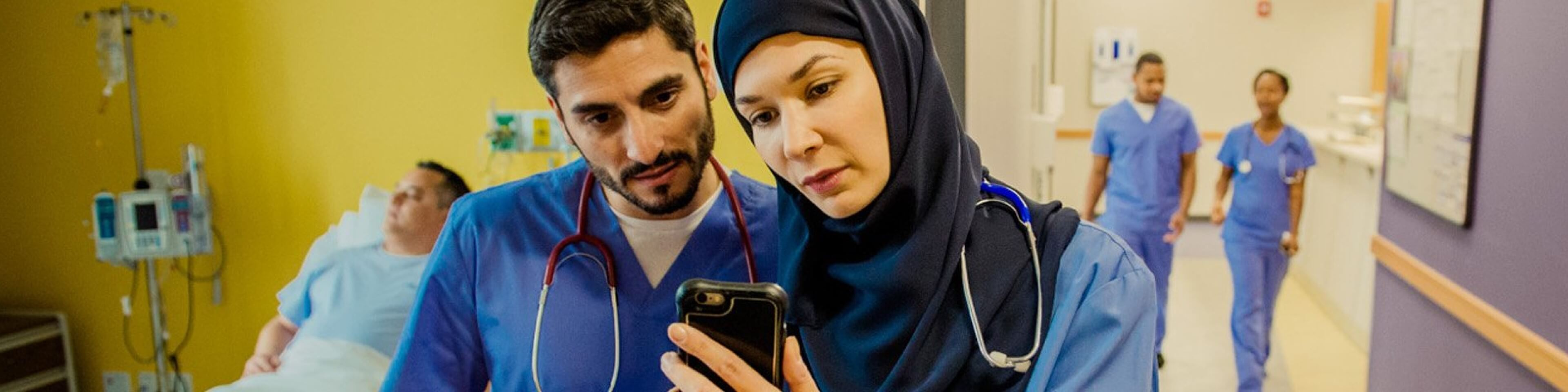 Doctors reviewing patient data on a secure mobile device