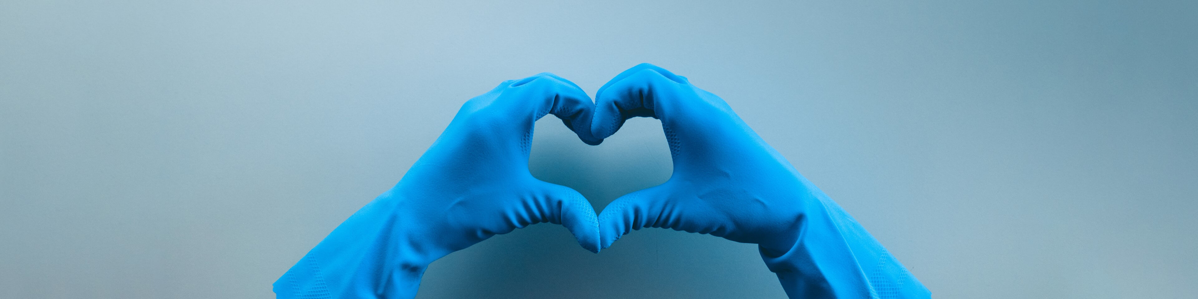 Nurse wearing protective gloves forming a heart