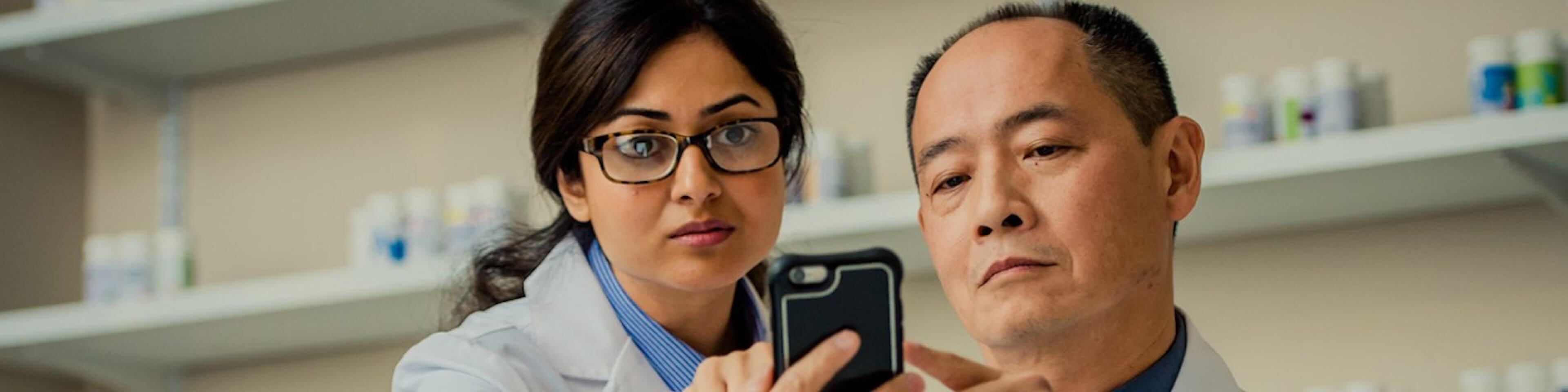 Pharmacists looking at data on a mobile device