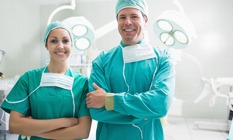 Two surgeons standing side-by-side in an OR