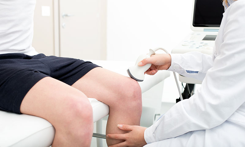 A doctor performing an ultrasound on a patient's knee