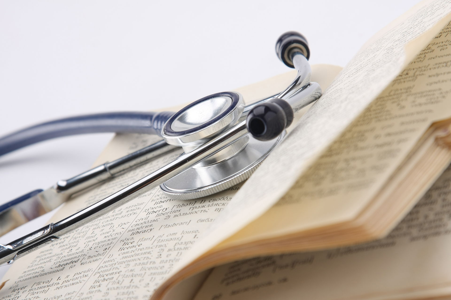 A stethoscope on an opened book, closeup