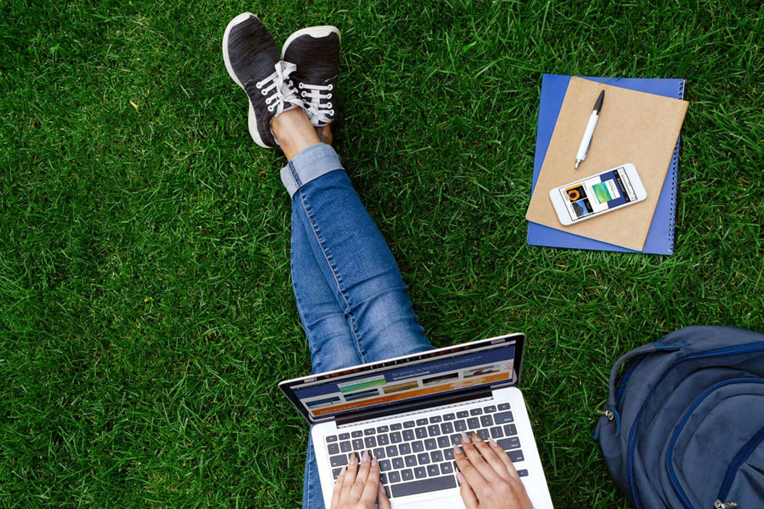 Student sitting on grass on laptop with backpack, phone, notebooks, and pen nearby