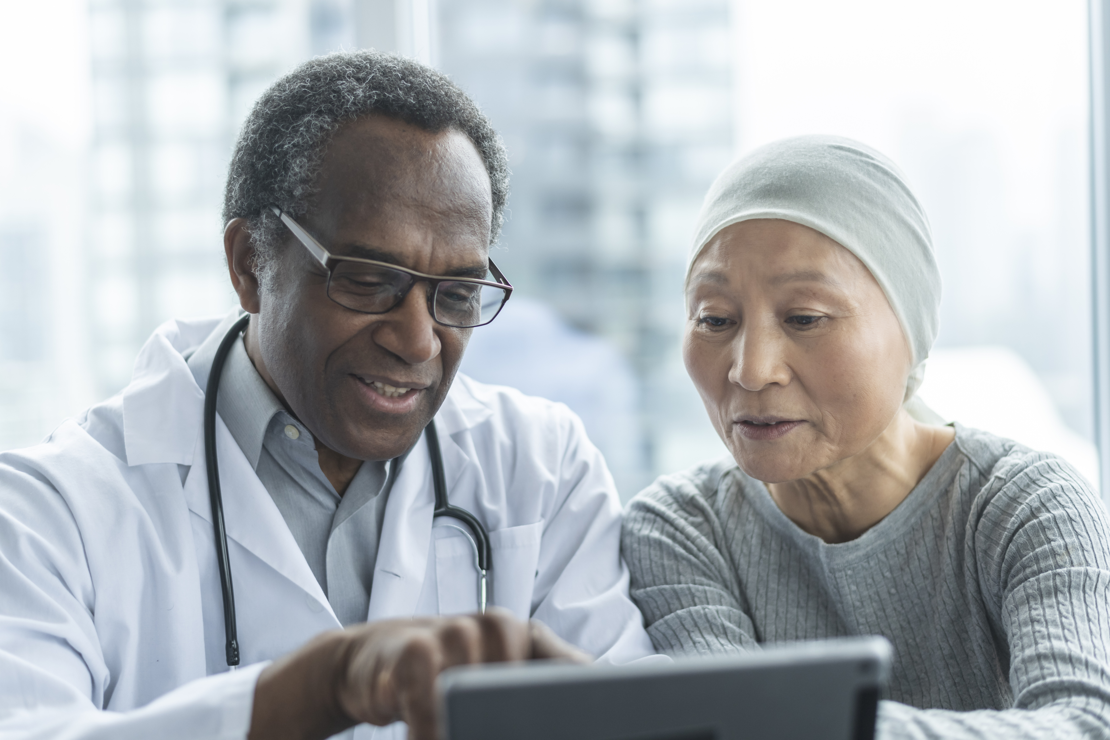 Doctor with cancer patient looking at a tablet