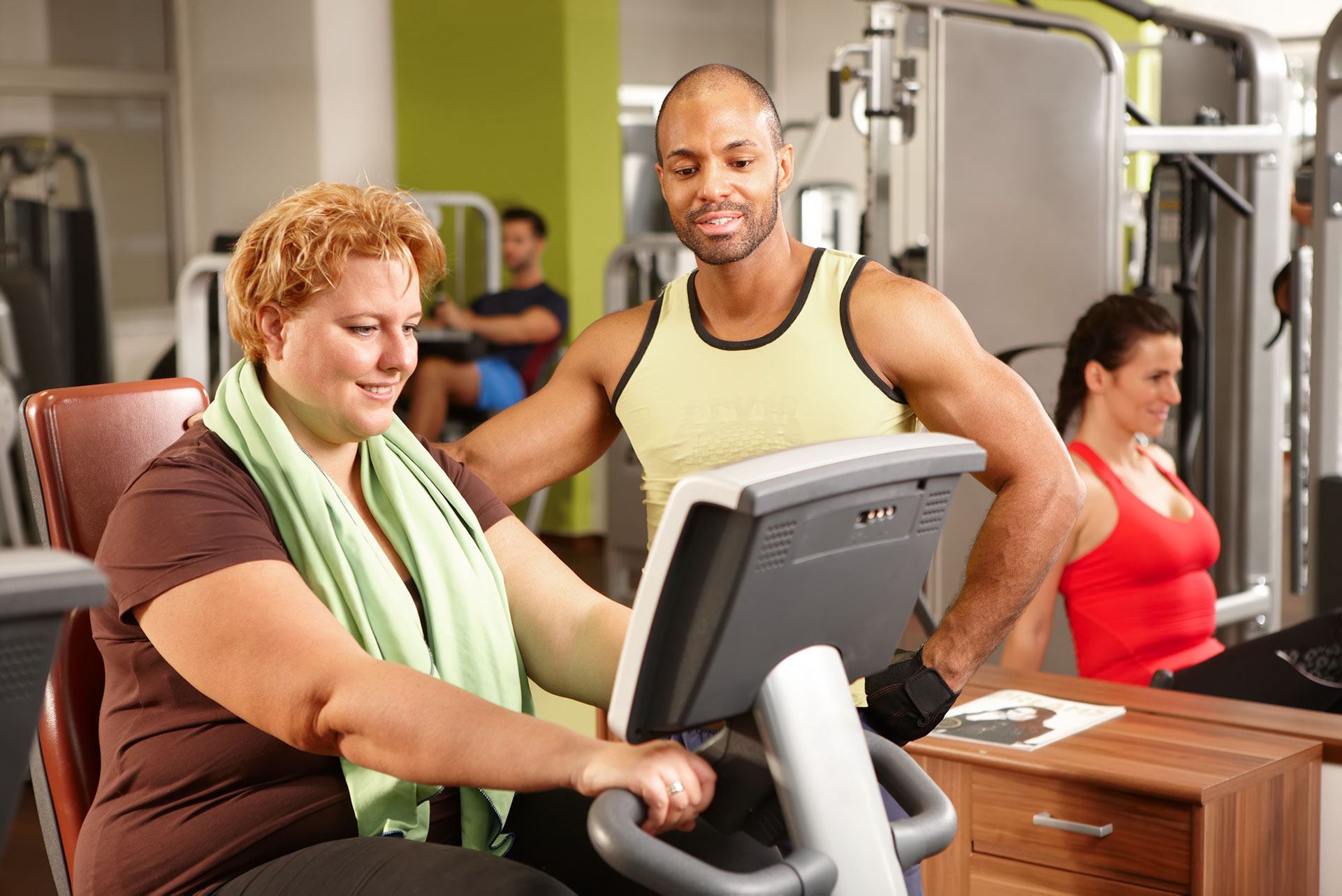Male personal trainer working with a female client on a stationary bike