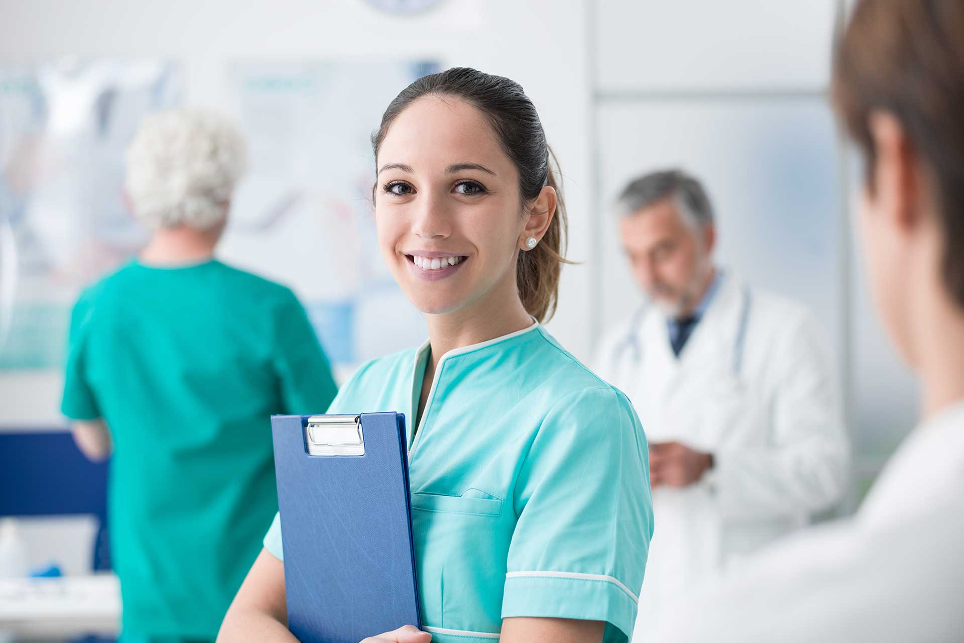 Nurse holding file to her chest and looking at camera in blurred background of hospital setting