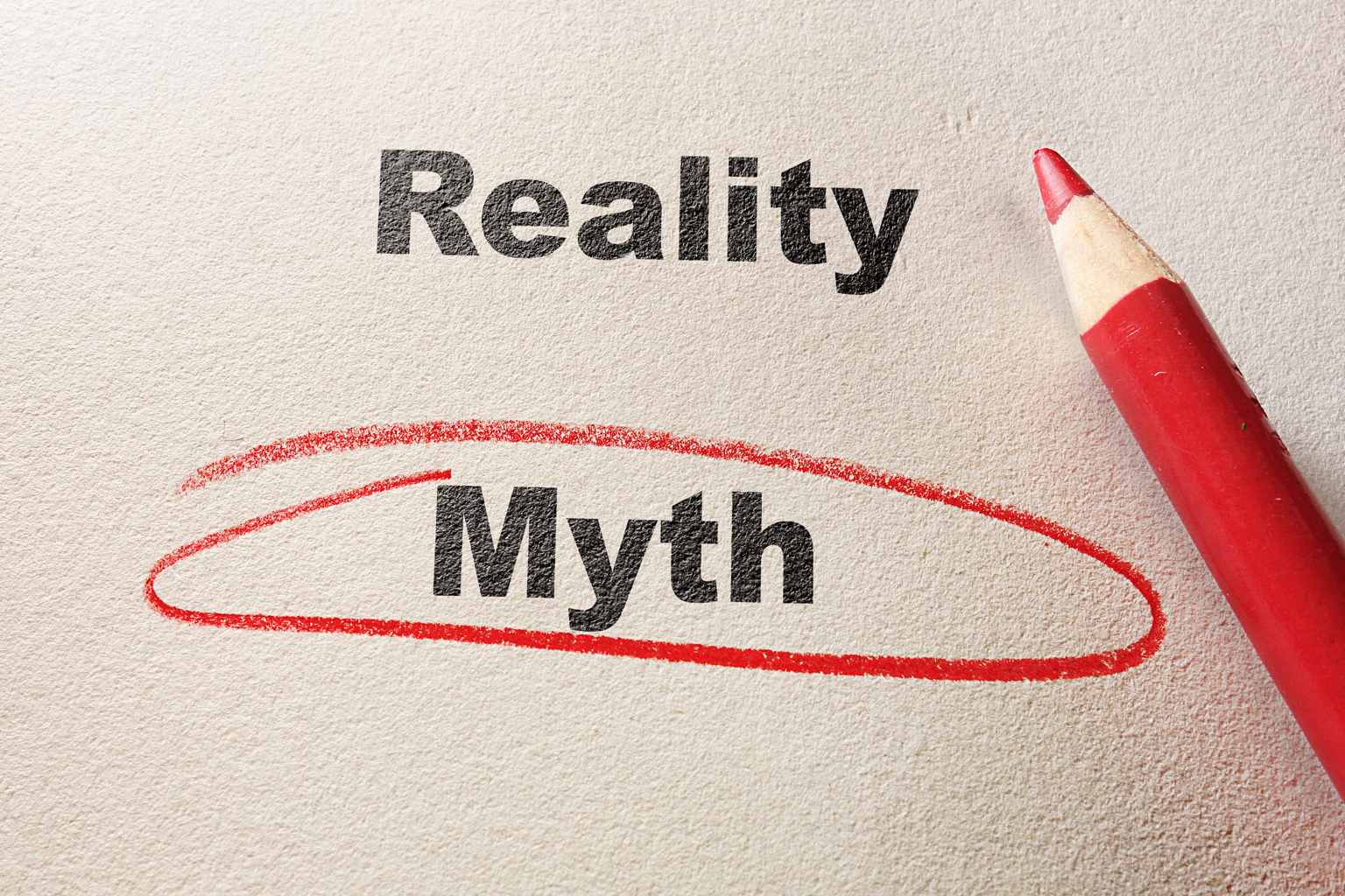 The words reality and myth with myth circled in red by a red pencil laying nearby