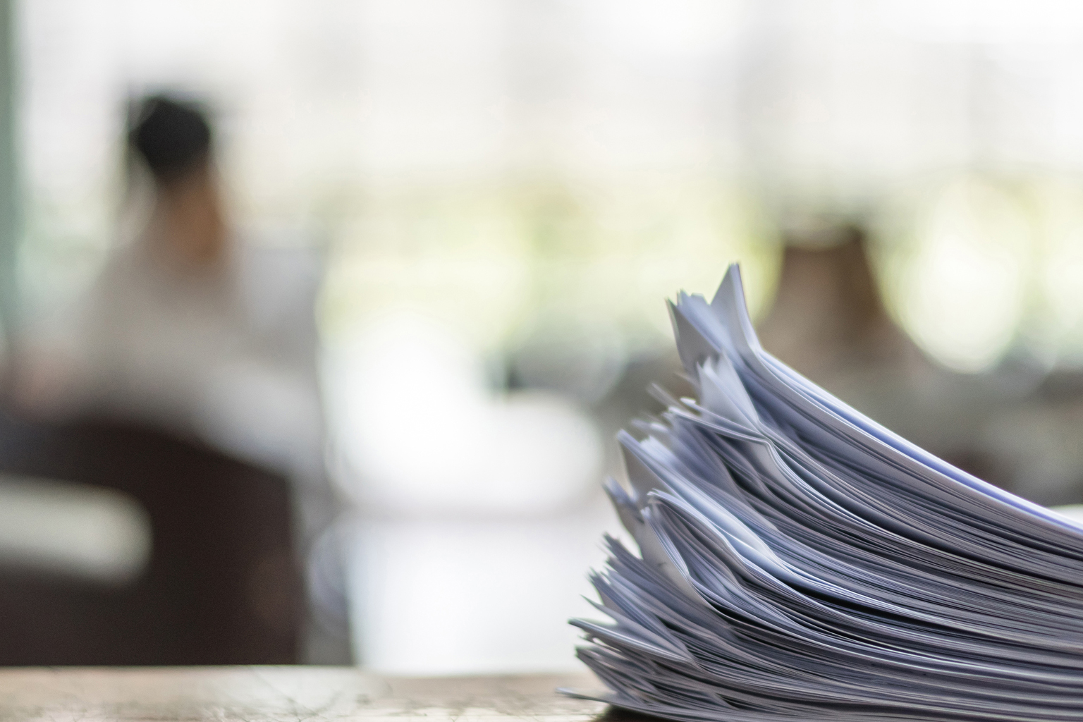 Stack of papers in foreground with two people in office blurred out in background