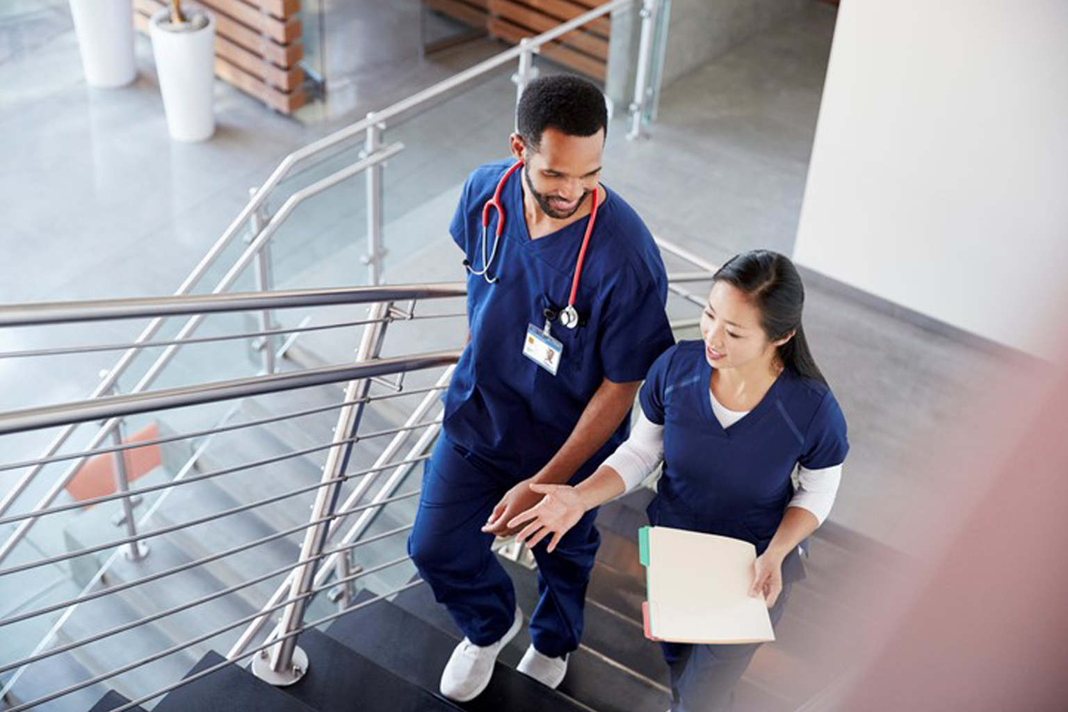 Two nurses walking up stairs in a hospital
