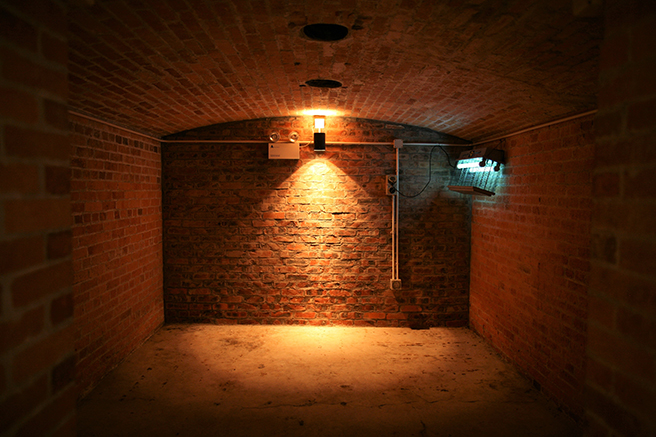 Empty brick room with safety light on the wall