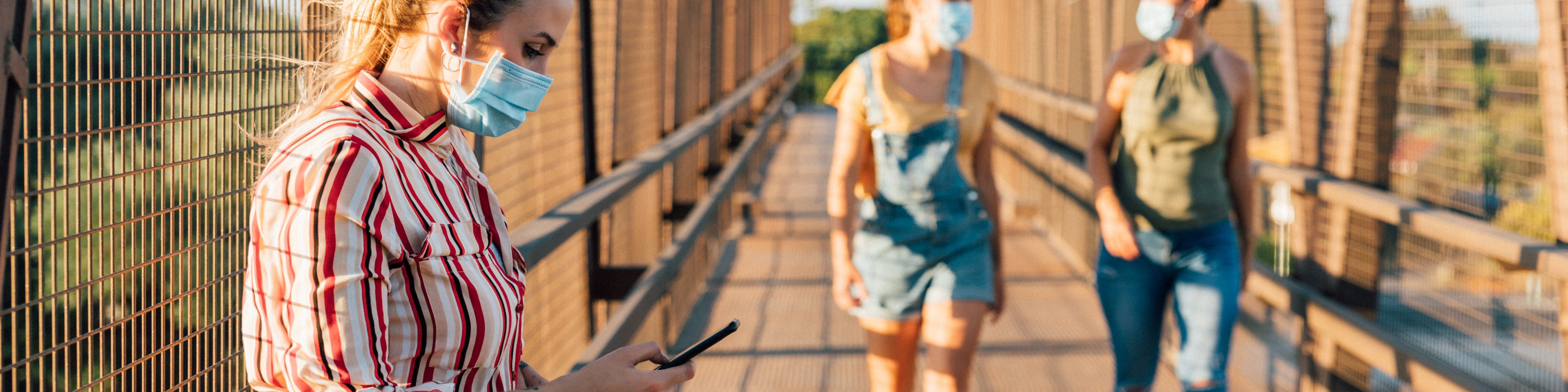 One young woman with medical mask and cellphone and two women with surgical mask walking and talking