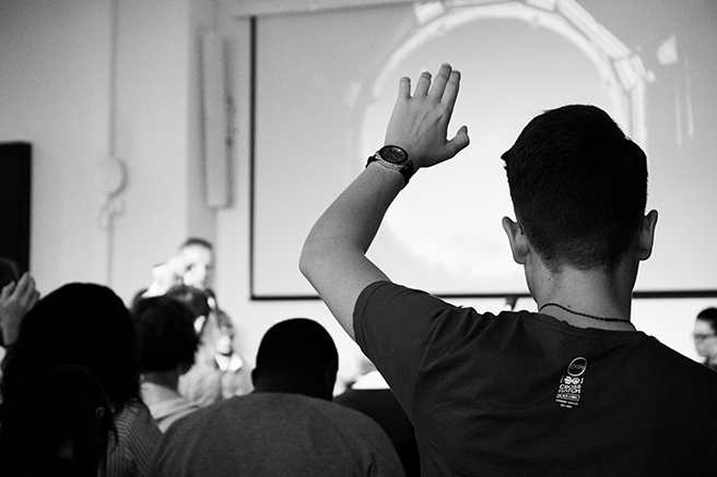 Black and white image of person with their hand raised at a conference presentation