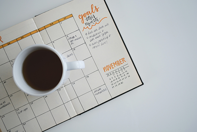 Birdseye view of monthly planner open to November with mug of coffee on top