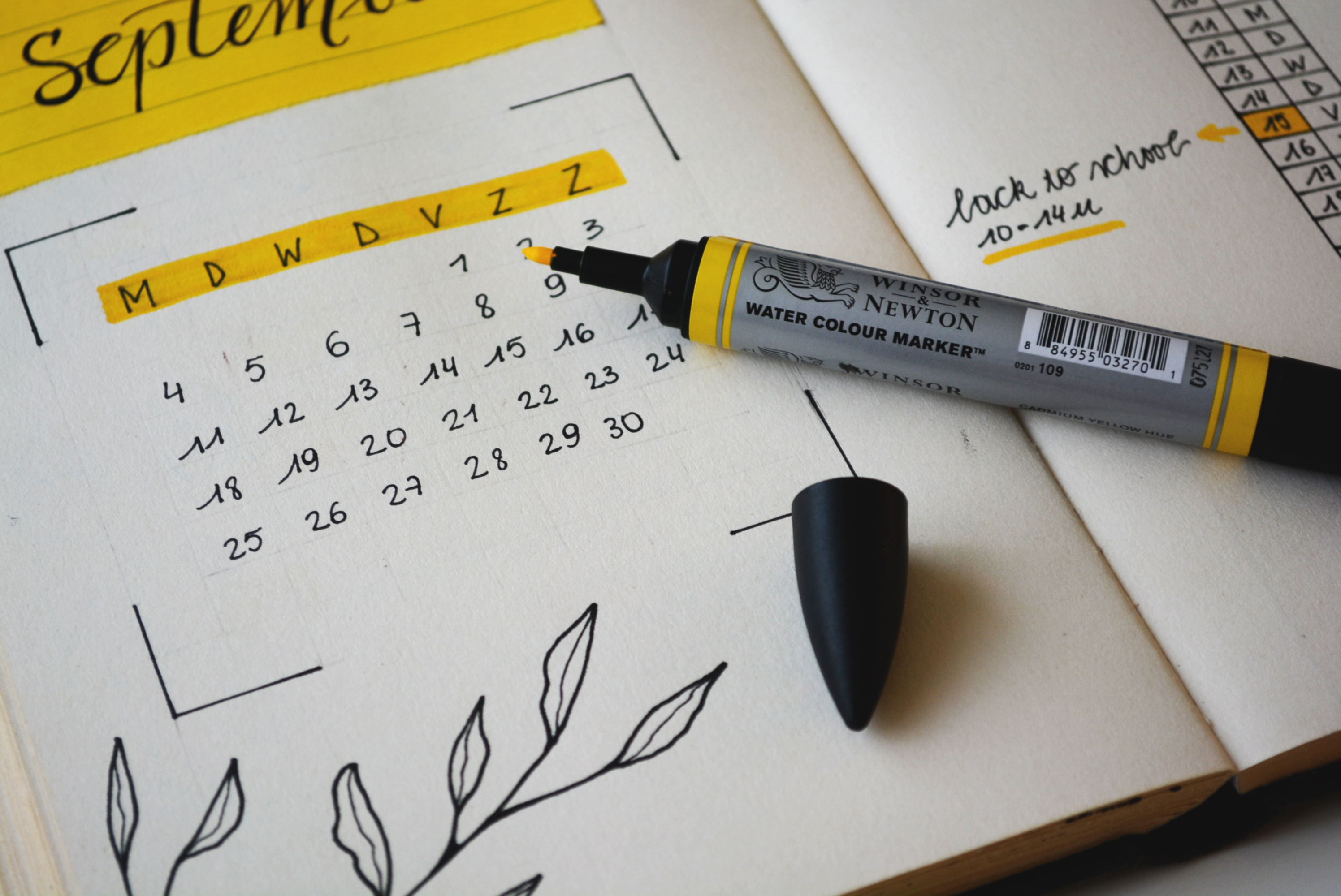 Monthly planner open to September with yellow highlighter sitting open on top
