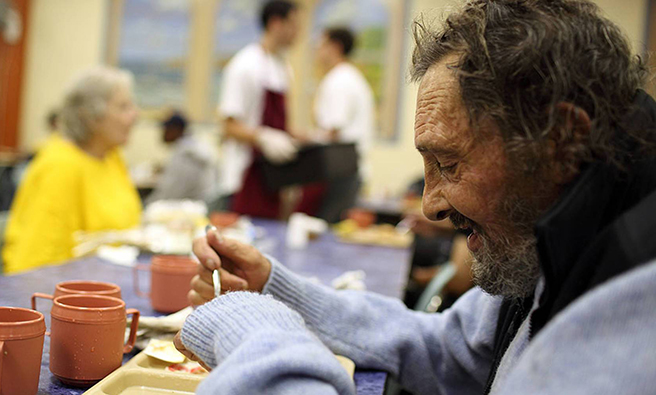 A homeless man eating a meal at a soup kitchen