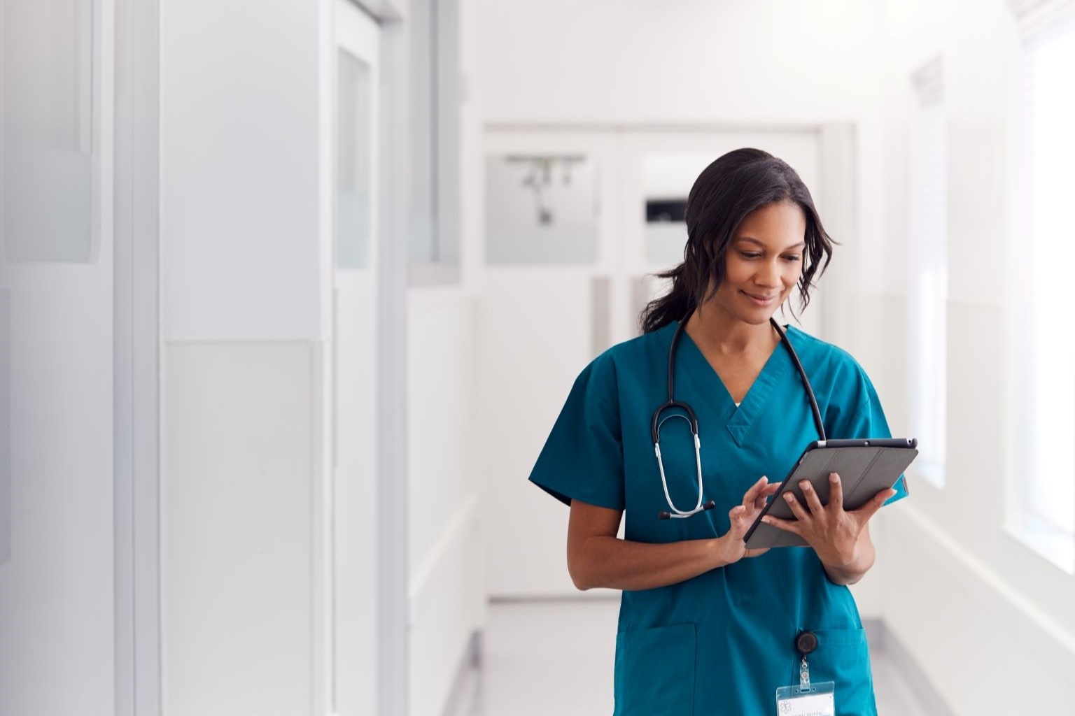 Nurse in hospital hallway reading on a tablet device