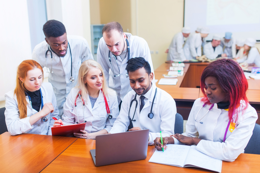 A mixed-race group of medical students in front of a laptop