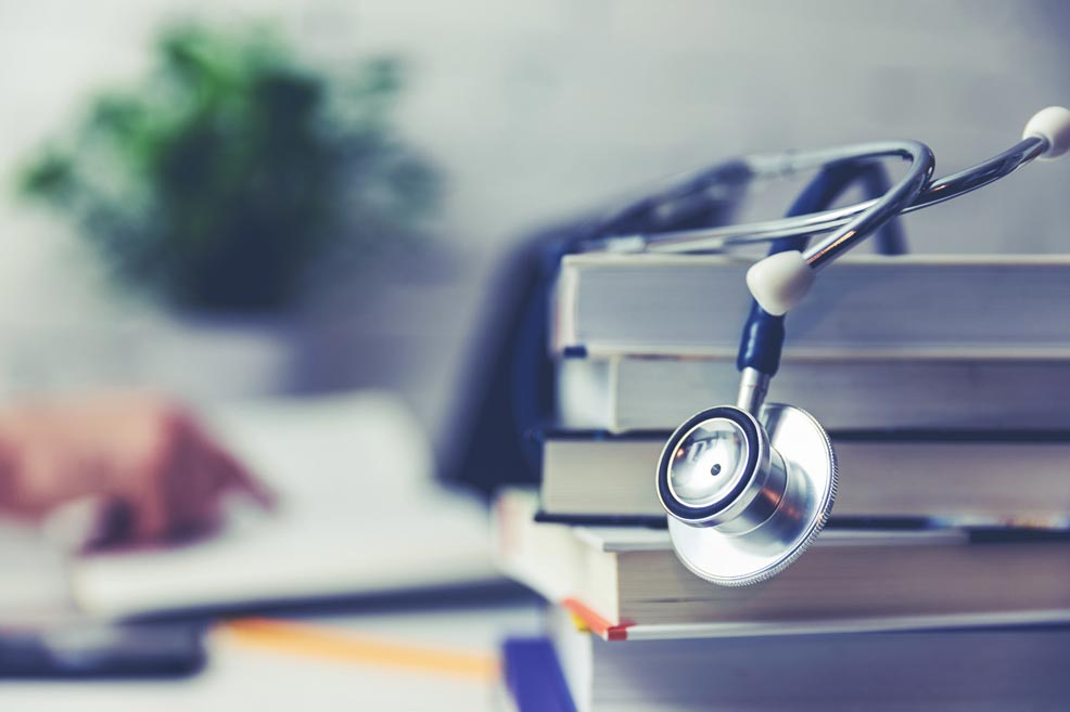 Stack of books with a stethoscope on top in the foreground with a hand pointing into a book in the background