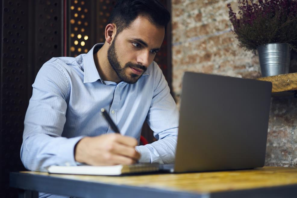 Man sitting at small table with laptop, notebook and pen, watching something on the screen