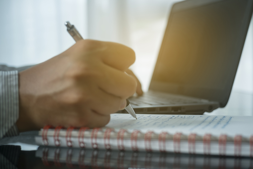 Close up on hand writing in notebook with laptop on the table behind