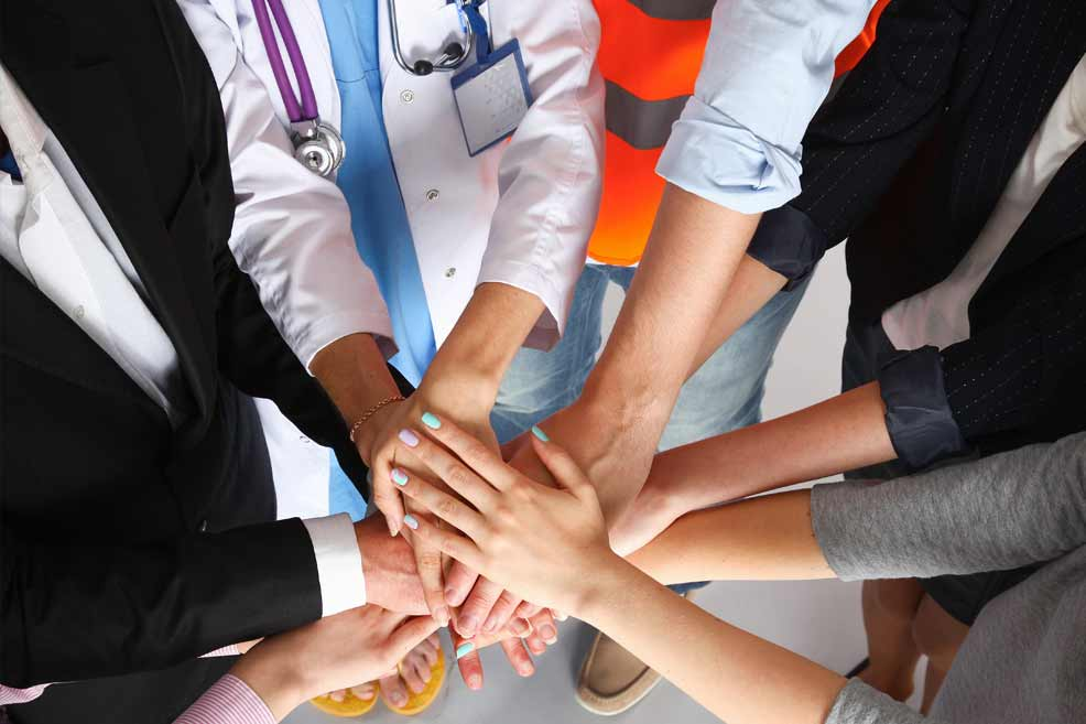 Various types of healthcare workers and staff putting their hands together in the middle