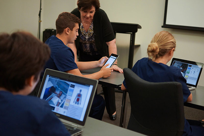 Nursing students sitting down in classroom with vSim for Nursing on their mobile and laptops