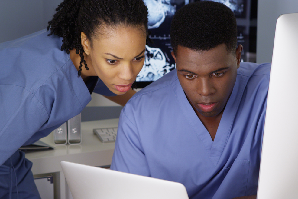 Two young nurses working together on multiple computers